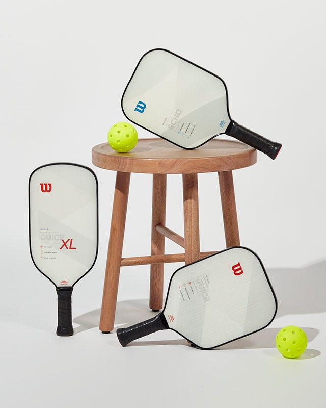 Wilson Pickleball paddles on a small stool
