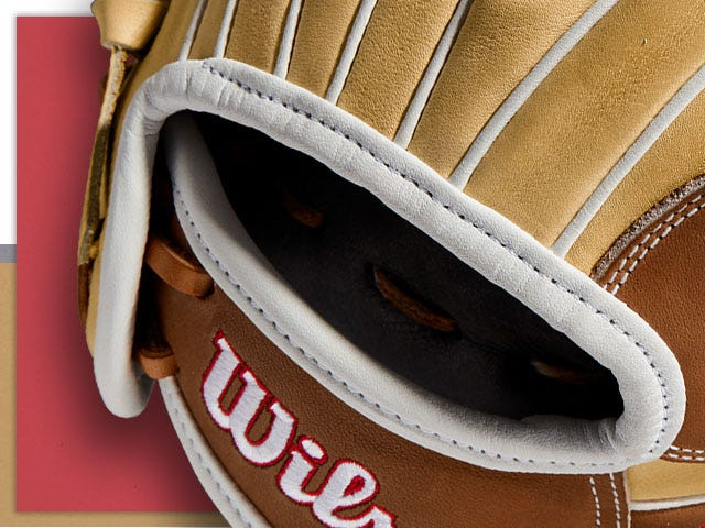 brown softball glove with white details and Wilson logo in white and red stitching