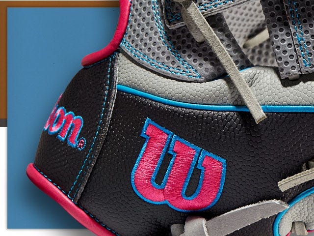close up of baseball glove with bright Wilson logo stitched in red and blue