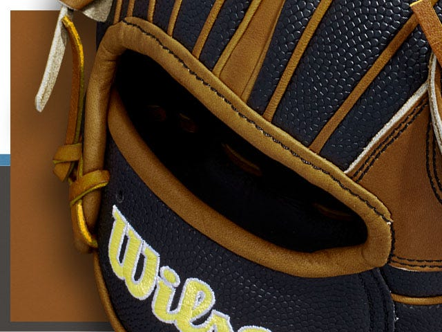 Close up of brown and black baseball glove with bright Wilson logo stitched in yellow