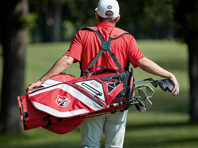 Man carrying Wilson Staff Golf Bag