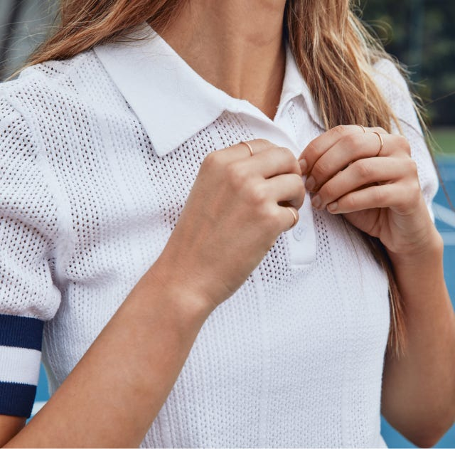 Woman buttoning up a polo shirt