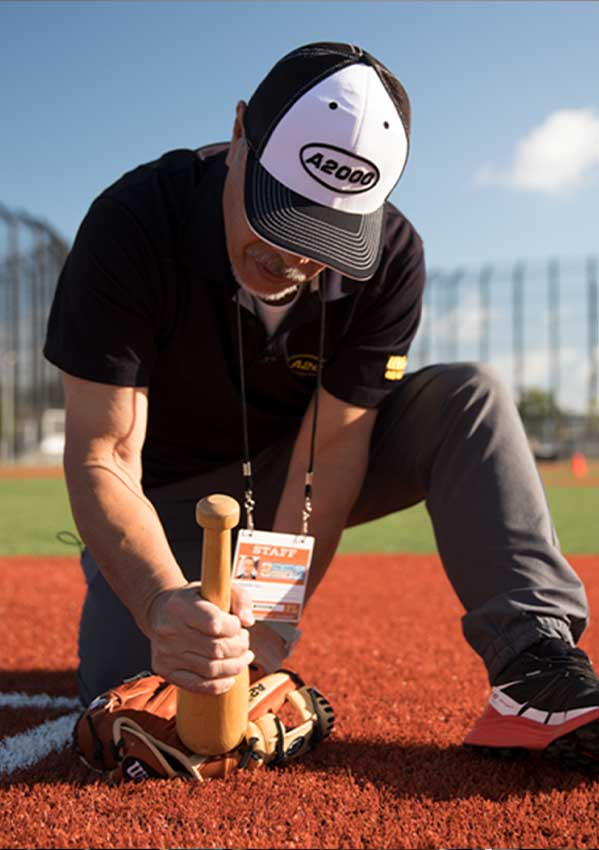 Wilson Ball Glove Master Craftsman Shigeaki Aso using a glove mallet to break in a Wilson glove on a baseball field