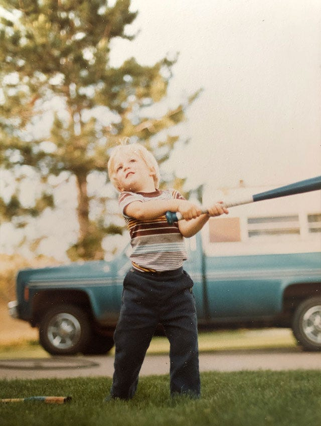 Childhood photo of Wilson Ball Glove Product Manager Ryan Smith swinging a baseball bat in his yard