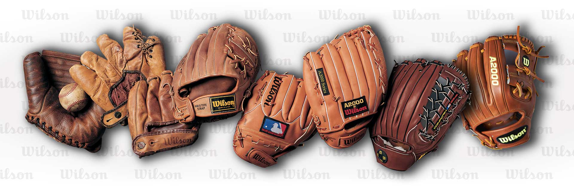 A line of eight gloves showing the evolution of Wilson ball gloves over the years from the first model to the newest