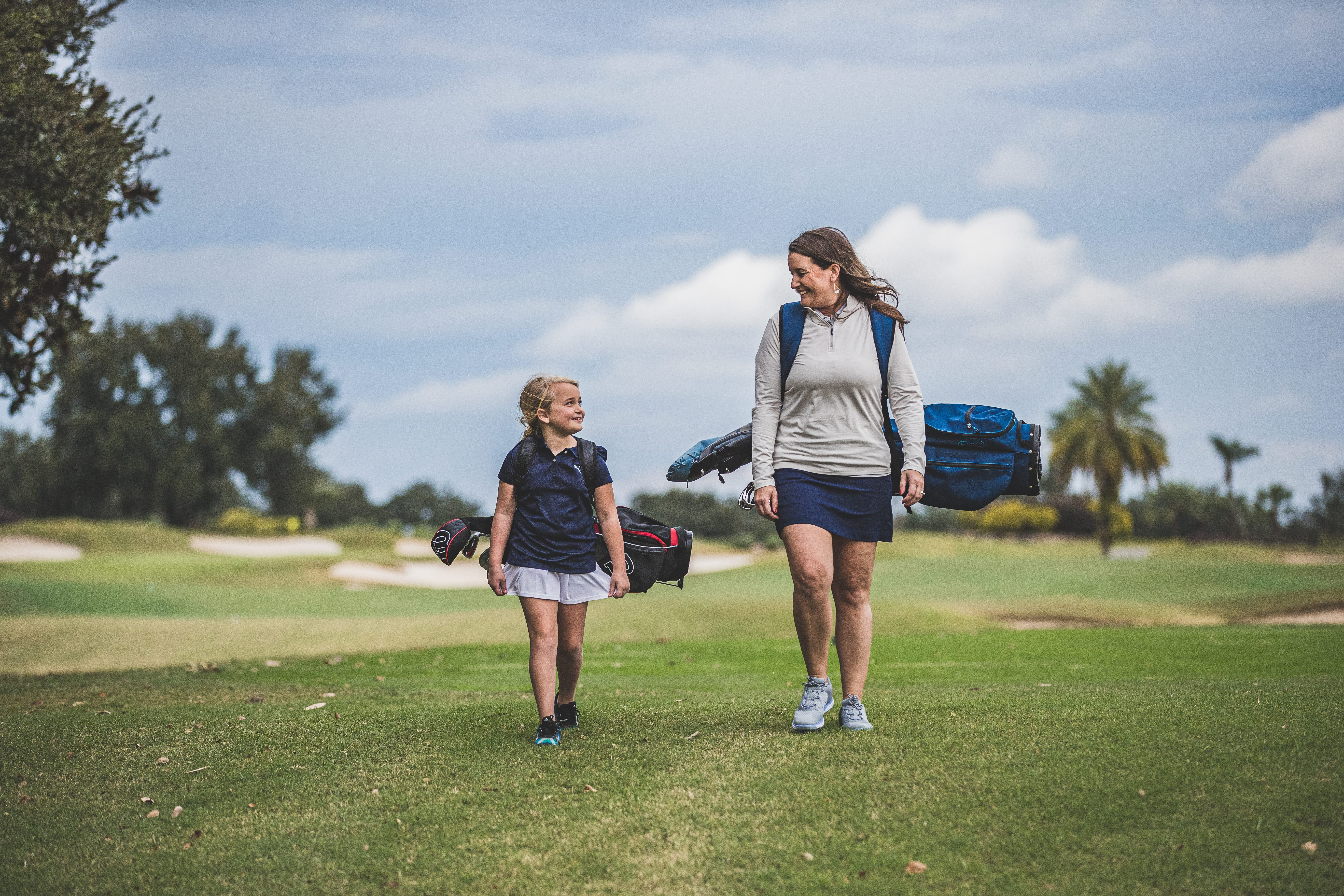 a mother and daughter on the fairway