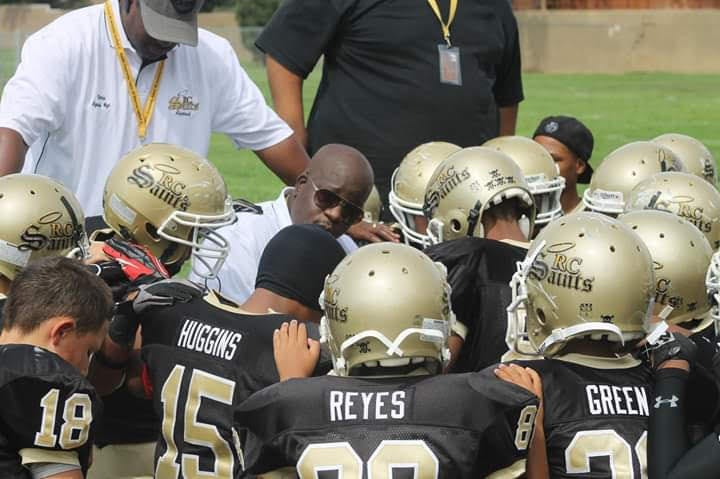 Art Hall speaking to a huddle of youth football players