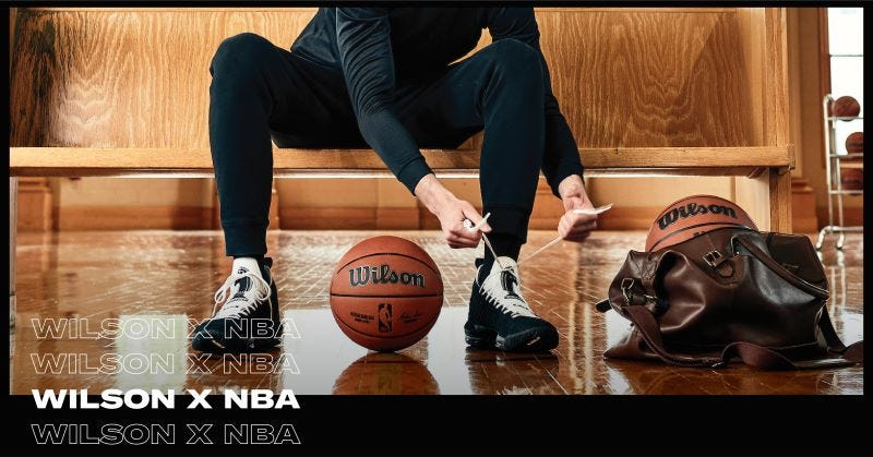 a basketball player tying shoes w/ ball on the ground next to him
