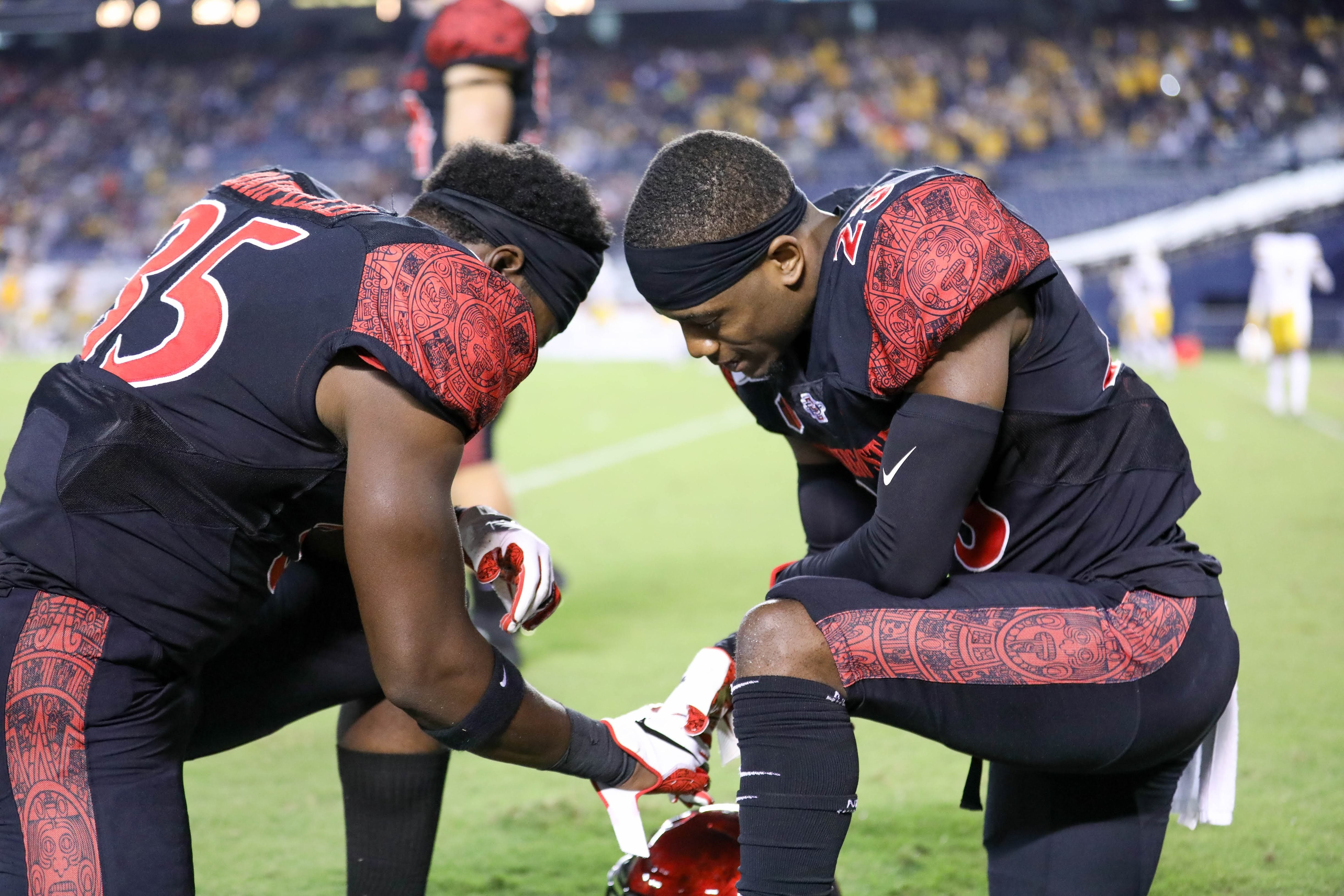 Darren Hall and a teammate kneeling on the field