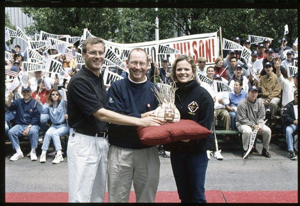 Considine, Wallace, and Davenport holding Wilson in front of crowded bleachers
