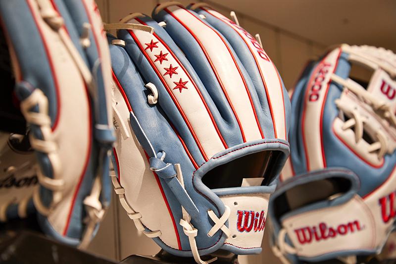 Shelf full of pale blue and white baseball gloves