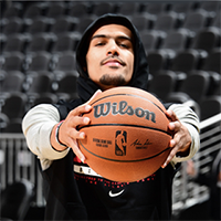 Trae Young holds a basketball in front of himself