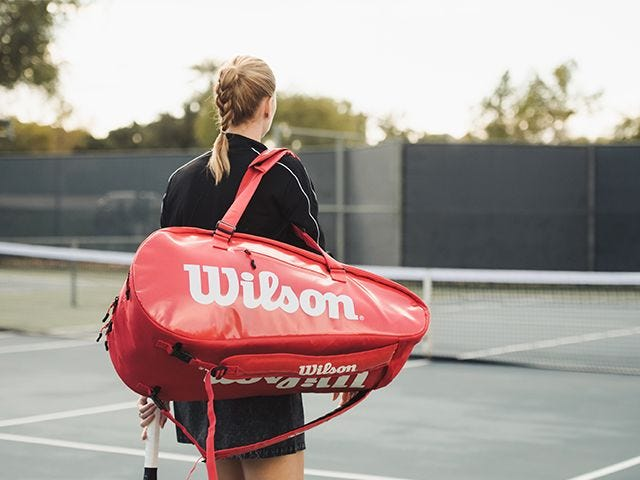 Player on court carrying tennis bag