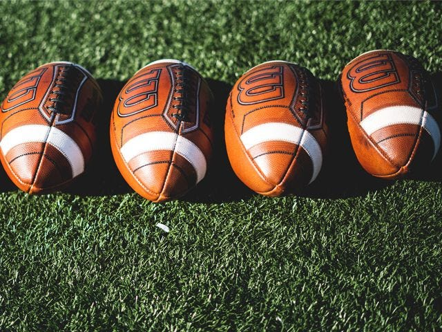 Four footballs lined up on the grass.