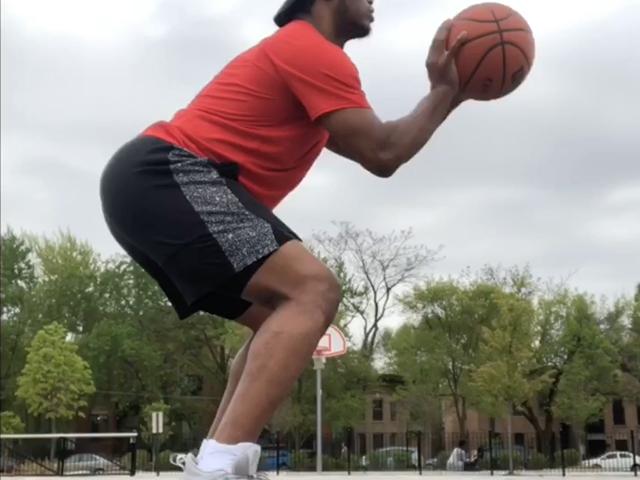 Side angle of trainer shooting a basketball