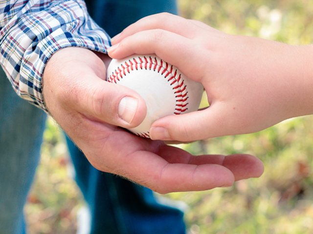 baseball being handed from dad to child