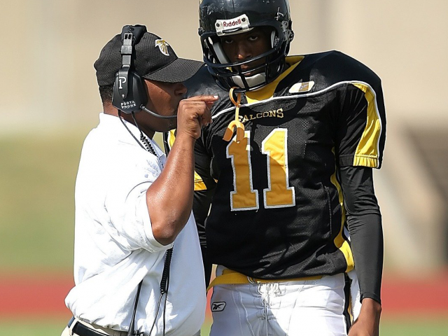 football coach talks to a high school player in uniform