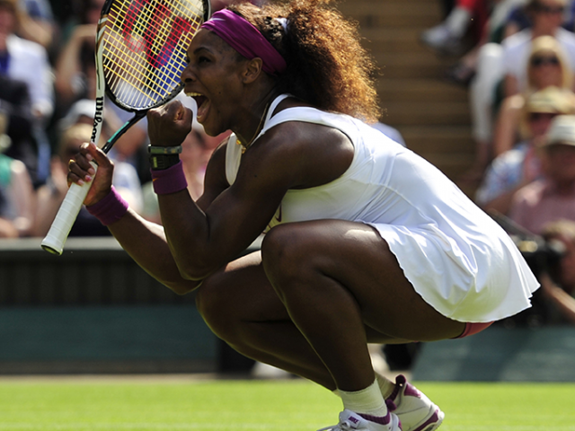 Serena Williams crouches on a tennis court after her Grand Slam victory