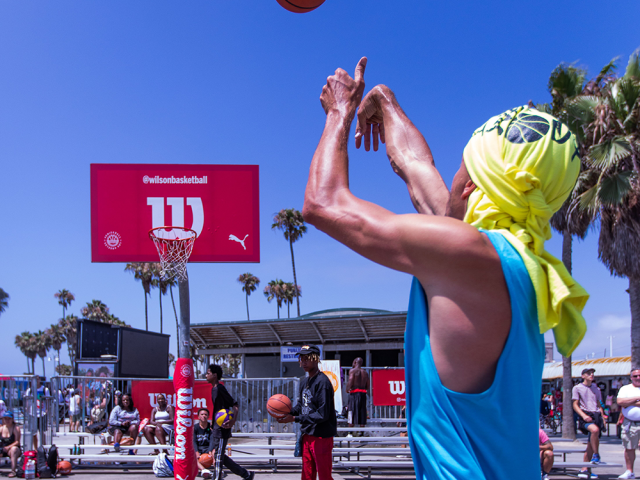 A man takes a basketball shot at a Wilson-branded backboard in Venice Beach