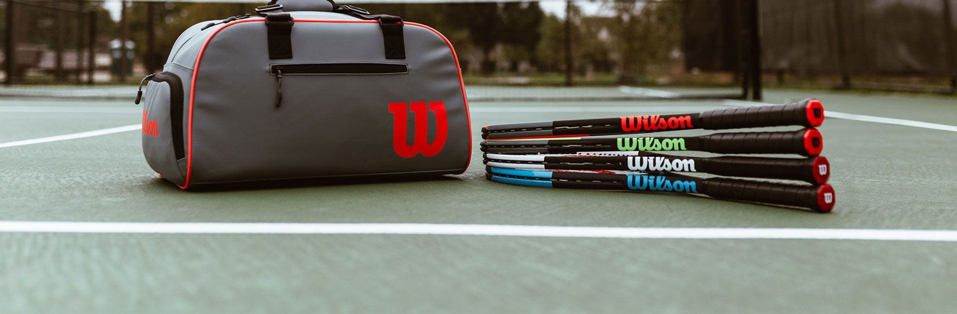 Clash duffel and family of Wilson rackets on tennis court
