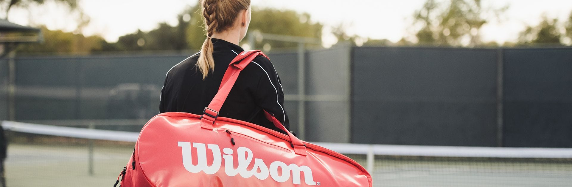 Player carrying tennis bag on court