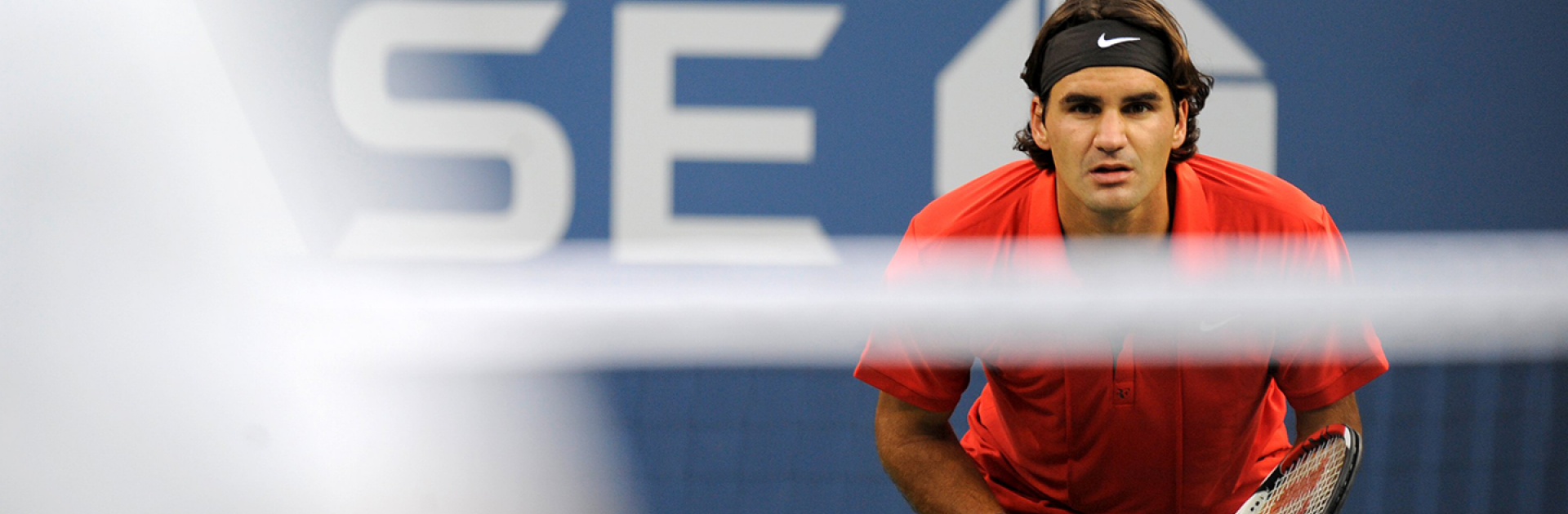Roger Federer looking at the camera over the net on the tennis court.