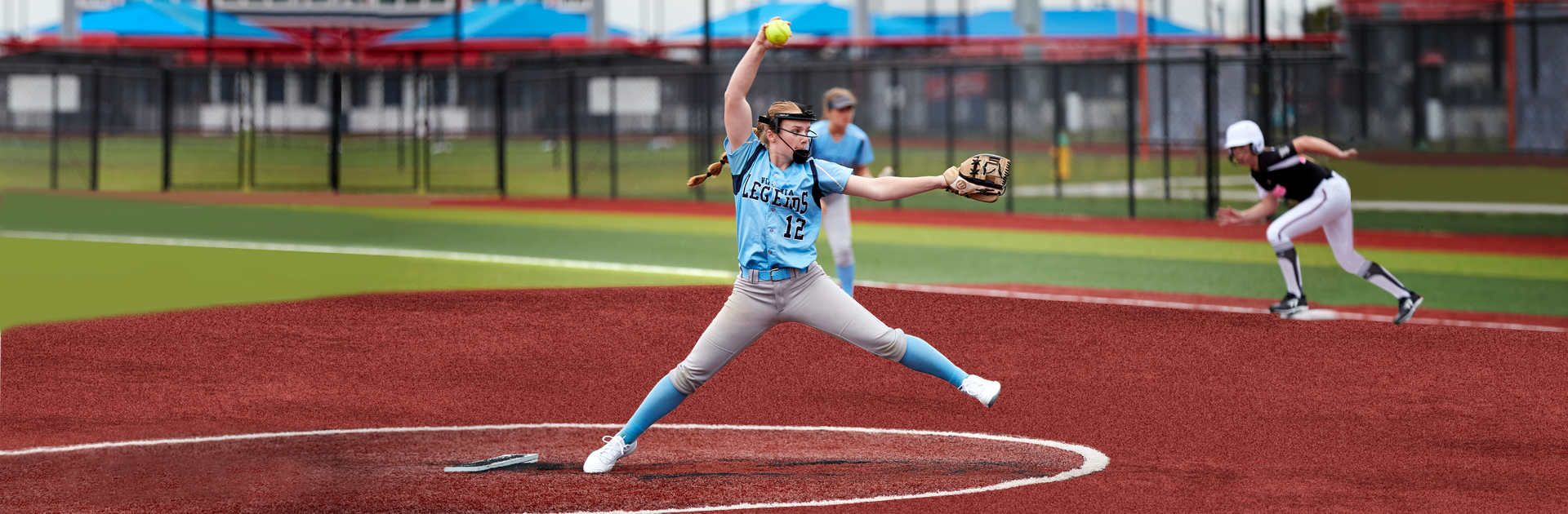 Woman in the middle of pitching a softball