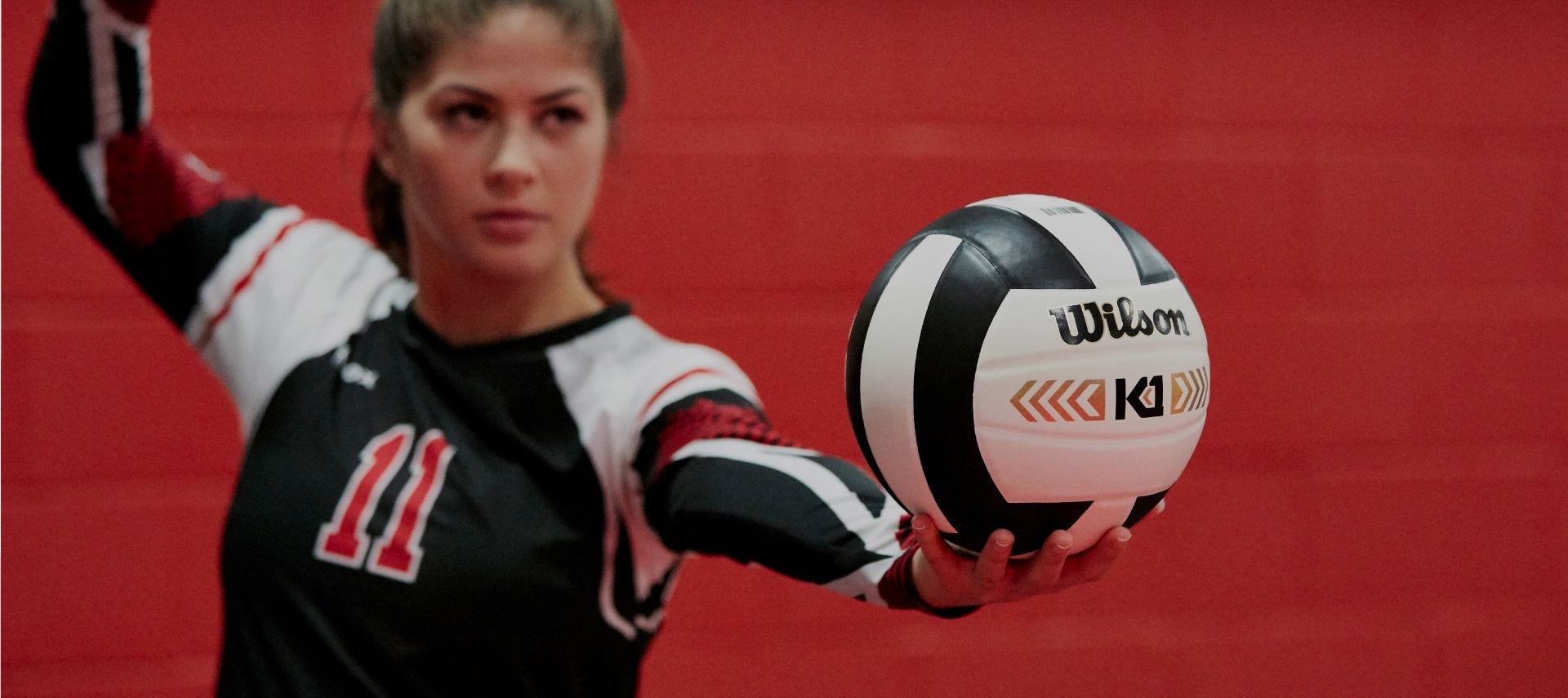 Indoor volleyball player setting up to serve