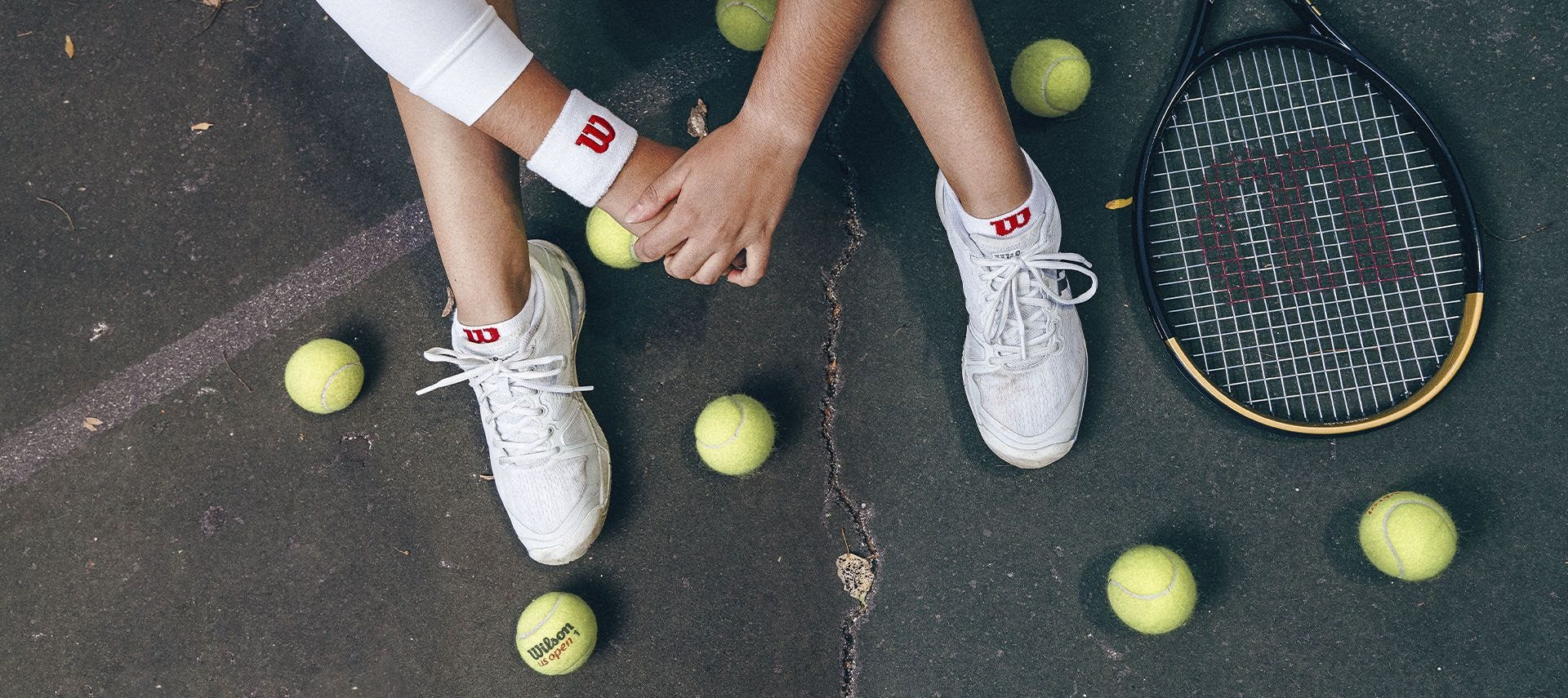 Aerial shot of a tennis player surrounded by tennis balls