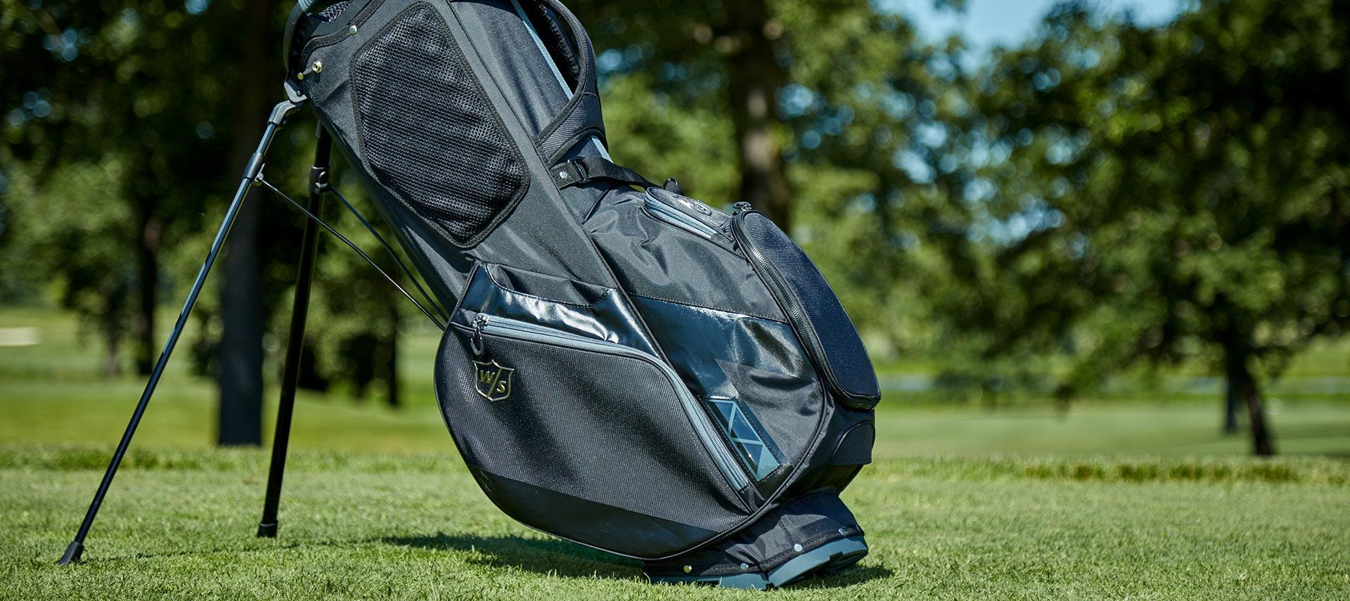 Full, side view of stand holding bag on golf course