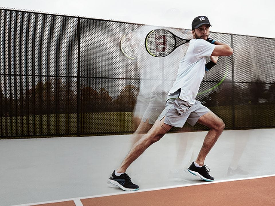 Player moving and swinging raacket on tennis court
